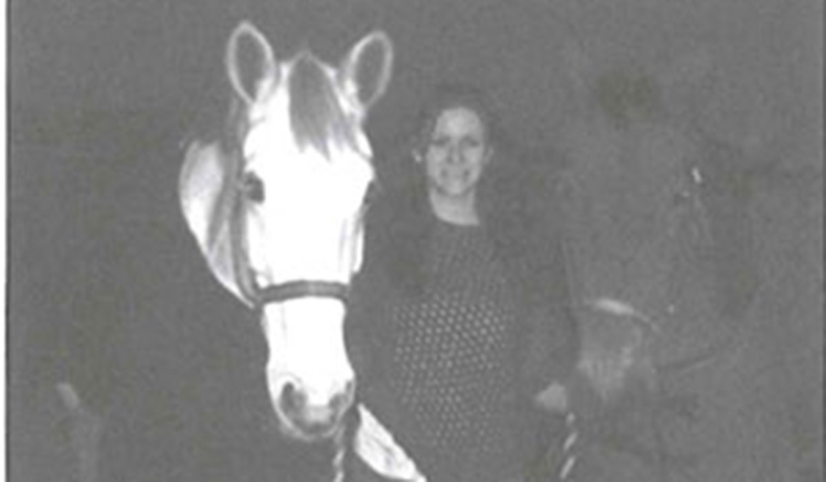 black and white photo of a woman and two horses